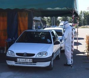 Empleats del sector sanitari realitzen proves PCR a diversos ciutadans des dels seus cotxes, aquest dimecres davant l'aparcament del camp de futbol Reino de León.