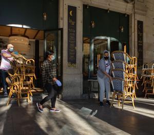 Dos treballadors recullen la terrassa d'un bar del centre de Barcelona.