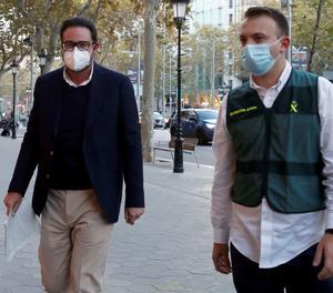 Agents de la Guàrdia Civil custodien l'exalt càrrec de CDC David Madí (esquerra) després de ser detingut