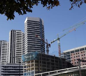 Un edifici en construcció al costat d'habitatges residencials