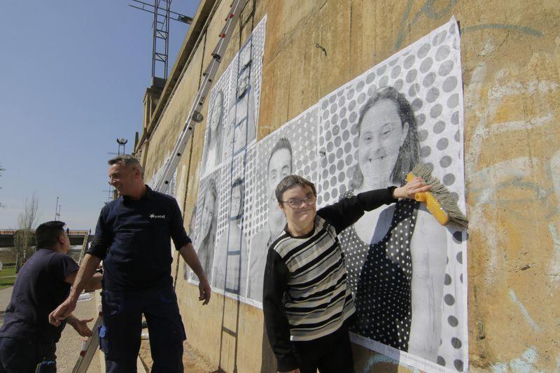 El muro de la canalización muestra más de un centenar de grandes retratos de felicidad para contagiar Lleida